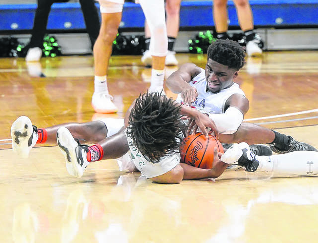 Lima Senior's Jourdyn Rawlins and Toledo Start's Cameron Moran compete for a loose ball during a Wednesday night Division I regional semifinal at John F. Savage Arena in Toledo last season.