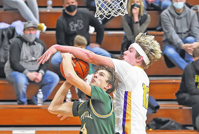 Ottoville's Kyle Manns goes up for a shot against Leipsic's Dillan Niese during Saturday night's game at Leipsic. See more game photos at LimaScores.com.
