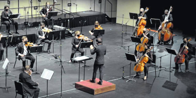 Lima Symphony Orchestra Maestro Andrew Crust, center, directs masked musicians who are socially distanced from one another while recording a video and audio performance for patrons.