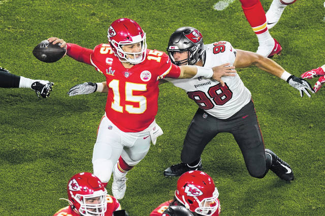 Kansas City Chiefs quarterback Patrick Mahomes (15) was under pressure by Tampa Bay's defense early in the Super Bowl, including this pass rush by the Buccaneers' Anthony Nelson (98) during the first half on Sunday night.
