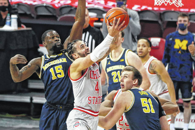 Ohio State's Duane Washington, center, shoots between Michigan's Chaundee Brown, left, and Austin Davis during the first half of an NCAA college basketball game Sunday, Feb. 21, 2021, in Columbus, Ohio. (AP Photo/Jay LaPrete)
