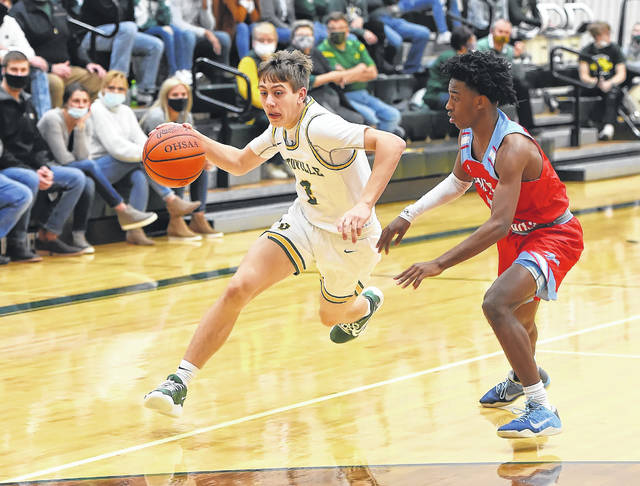 Ottoville's William Miller drives against Lima Central Catholic's DeMarr Foster during Friday night's game at Ottoville. See more photos at LimaScores.com.