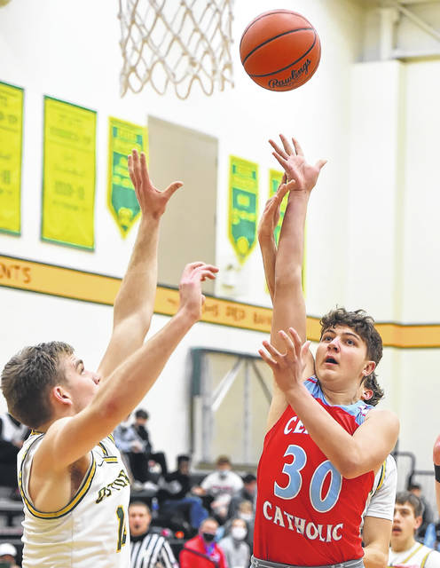 Lima Central Catholic's Carson Parker puts up a shot against Ottoville's Josh Thorbahn during Friday night's game at Ottoville.