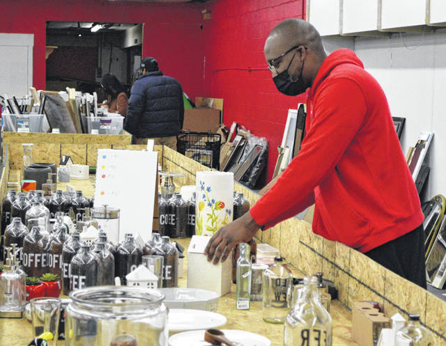 Brandon Barrett, CEO of NOLO Pallets, checks out some of the bins of merchandise at his store.