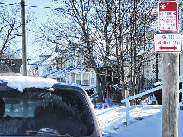 A sign warns drivers to move their vehicles after 4 inches of snow or more along Lima's Marian Avenue on Wednesday morning. Lima officials reminded drivers to make a clear path for snowplows after a storm earlier this week and more snowfall predicted Thursday night.