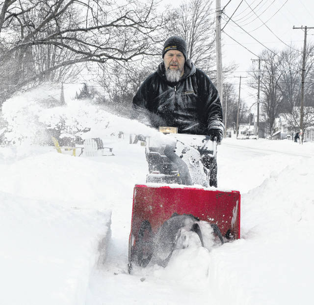 Roger Thomas helps clear sidewalks for neighbors on Leeson Avenue in Van Wert on Tuesday morning. The region received nearly a foot of snow in a 24-hour period.