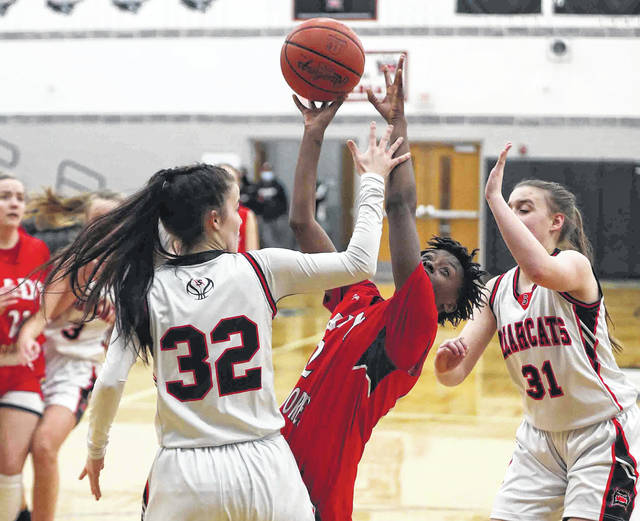Perry's Mi'auni Hall puts up a shot against Spencerville's Emma Leis (32) and Heidi Keller during Thursday night's sectional semifinal at Spencerville. See more photos at LimaScores.com.