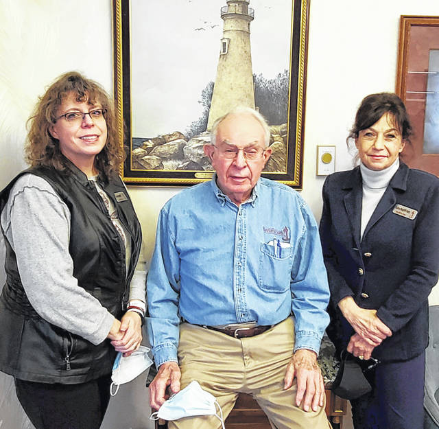 From left, Becky Bayliff, John Bayliff and Valery Bayliff Fultz hold their masks while posing with a favorite picture of a lighthouse at Bayliff & Son Funeral Home in Cridersville. Smaller services joined masks and disinfectants as becoming commonplace at funeral homes throughout the pandemic.