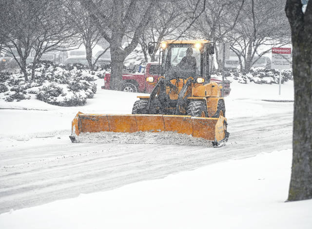 A snowplow driver tackles the snow during Monday's snowfall at Mercy Health-St. Rita's Medical Center.
