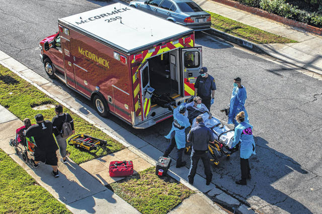Los Angeles paramedics load a potential COVID-19 patient in the ambulance before transporting him to a hospital as a family walks by.