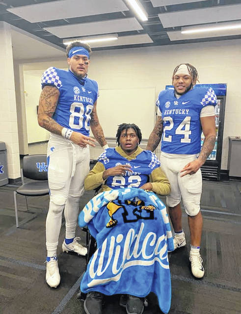 Kentucky tight end Keaton Upshaw (88), a Lima Senior graduate, and running back Chris Rodriguez (24), are shown with teammate Chris Oats after a game last season. Oats suffered an undisclosed medical emergency which necessitated him spending significant time at a rehab facility.