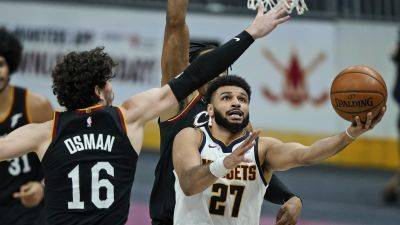 The Denver Nuggets' Jamal Murray (27) drives to the basket against the Cavaliers' Cedi Osman during Friday night's game in Cleveland. (AP Photo)