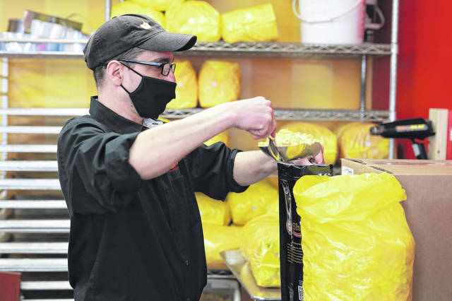 Mark Slotter, store manager of Shirley's Gourmet Popcorn Compant in Bluffton, fills bags of popcorn for the visitors of the chocolate walk on Thurdsday afternoon.