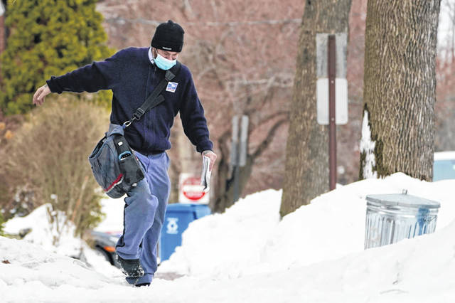 Postal carrier Josiah Morse steps carefully on a snowy sidewalk in Portland, Maine. The U.S. Postal Service's stretch of challenges didn't end with the November general election and tens of millions of mail-in votes. The pandemic-depleted workforce fell further into a hole during the holiday rush, leading to long hours and a mountain of delayed mail.