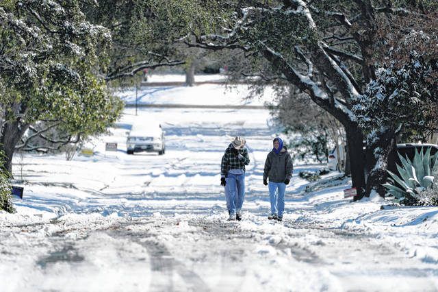 Residents walk through snow Monday in San Antonio, Texas. San Antonio received 3-5 inches of snow over night. A winter storm dropping snow and ice also sent temperatures plunging across the southern Plains, prompting a power emergency in Texas a day after conditions canceled flights and impacted traffic across large swaths of the U.S.