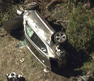 A vehicle rests on its side after a rollover crash Tuesday involving golfer Tiger Woods along a road in the Rancho Palos Verdes section of Los Angeles.
