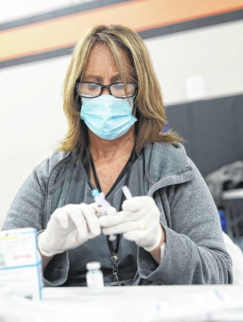 Allen County Public Health Director of Nursing Deb Roberts prepares a dose of vaccine during a clinic held Tuesday afternoon at Elida High School.