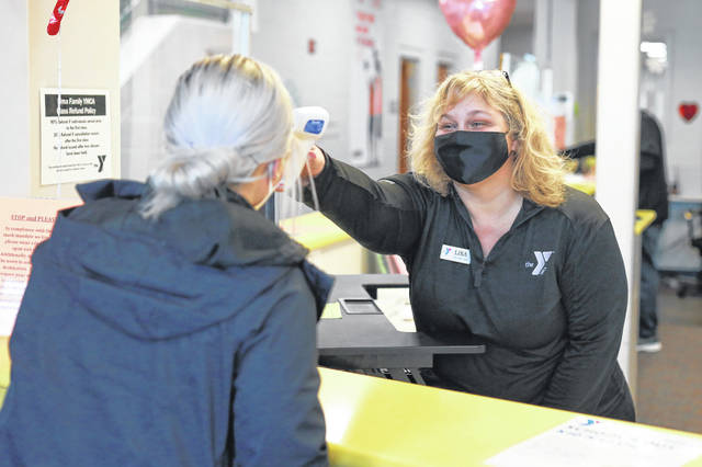 Lisa Pakkidis takes a temperature at the Lima Family YMCA.