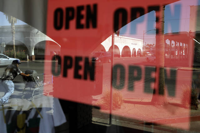 ADVANCE FOR RELEASE MARCH 14, 2021, AND THEREAFTER - FILE - In this June 30, 2020, photo, a man passes a clothing shop with open signs in the window in Calexico, Calif. A year after the first coronavirus shutdowns, many U.S. states and cities are still struggling with a silent side effect: Public records have become harder to get. As states prepared to reopen their economies following coronavirus shutdowns last spring, The Associated Press asked governors across the U.S. for records that could shed light on how businesses and health officials influenced their decisions. (AP Photo/Gregory Bull, File)