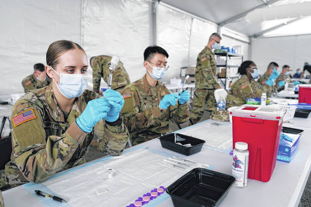 Army health specialists fill syringes with the Pfizer COVID-19 vaccine March 9 in Miami. Despite the clamor to speed up the U.S. vaccination drive against COVID-19, the first three months of the rollout suggest faster is not necessarily better.