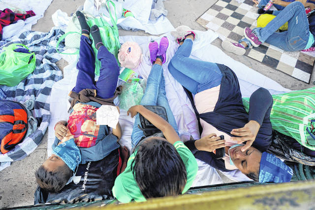Migrants rest in a gazebo at a park after a large group of deportees were pushed by Mexican authorities off an area they had been staying after their expulsion from the U.S. on Saturday in Reynosa, Mexico. A surge of migrants on the Southwest border has the Biden administration on the defensive. The head of Homeland Security acknowledged the severity of the problem Sunday but insisted it's under control and said he won't revive a Trump-era practice of immediately expelling teens and children.