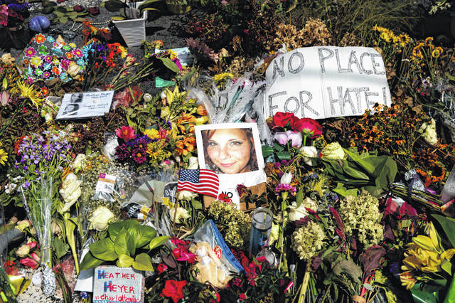 """A photo is shown Aug. 16, 2017, of Heather Heyer, who was killed during a white nationalist rally, surrounded with flowers at a memorial paying tribute to her life at the Paramount Theater, Charlottesville, Va. In a nation founded on whiteness, experts share perspective on whether it can be discussed. If white people want the future to be different, said Rev. Susan Chorley, a Boston area pastor, they have to be willing to look at the past and the present. """"I think it's on us,"""" she said. (AP Photo/Evan Vucci)"""