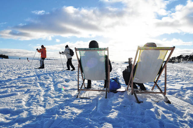 People sit in the sunshine as others ski by, during a sunny winter day on waterfront ice of Helsinki, Finland on Valentine's Day February 14, 2021.  In a year of untimely deaths from the coronavirus, economic decline and social loneliness, The World Happiness Report revealing the world's happiest countries shows Friday March 19, 2021, Nordic countries topped the index, with Finland leading for the fourth consecutive year. (Jussi Nukari/Lehtikuva via AP)
