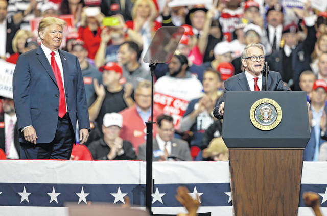 FILE - In this Nov. 5, 2018, file photo, President Donald Trump, left, listens as then candidate Mike DeWine speaks at a campaign rally in Cleveland. The DeWine, the current Republican Ohio Governor, has said he'd accept an endorsement for next year's run for governor from former President Trump. (AP Photo/Tony Dejak, File)