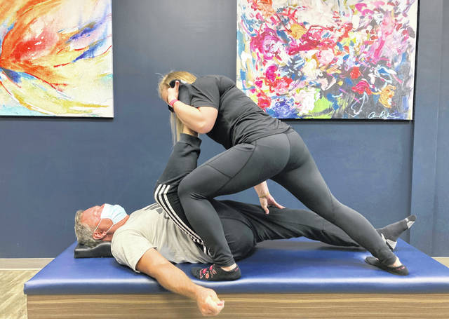 Tara Albarron, 32, works with client Ron Bryant, 55, of Beaver Creek, Ohio, during an assisted stretching session at StretchLab in Centerville, Ohio, on March 8, 2021.  Assisted stretching is intended to improve range of motion, flexibility and circulation, among other benefits. (AP Photo/Julie Carr Smyth)