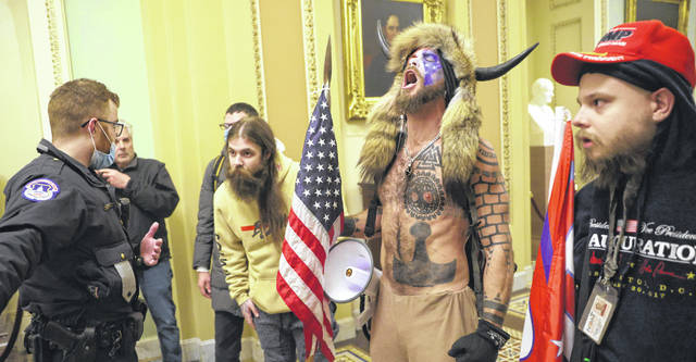 """Jacob Chansley (in horns), dubbed the """"QAnon Shaman, """" interact with Capitol Police inside the U.S. Capitol Building on Jan. 6. Chansley said a prayer after arriving. He's now one of the first people charged in the event."""