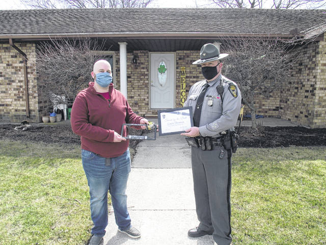 """Gage Homan joined the """"Saved by the Belt"""" Club. Homan, left, received a certificate and license plate holder from Lt. John D. Westerfield from the Wapakoneta Post of the Ohio State Highway Patrol."""