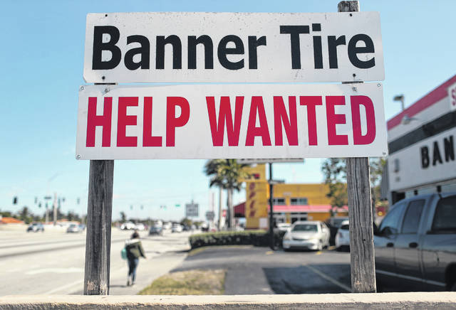 A 'Help Wanted' sign is posted in front of a business on February 4, 2021 in Miami. (Joe Raedle/Getty Images/TNS)