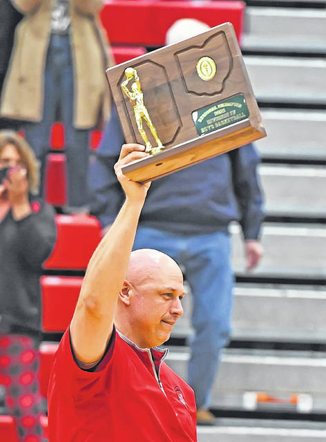 Columbus Grove Head Coach Chris Sautter raises the Division IV regional championship trophy that the Bulldogs received after defeating New Bremen to earn a state berth. This is Sautter's second trip to state as a head coach. He coached Ada to a final fourth berth in 2009.