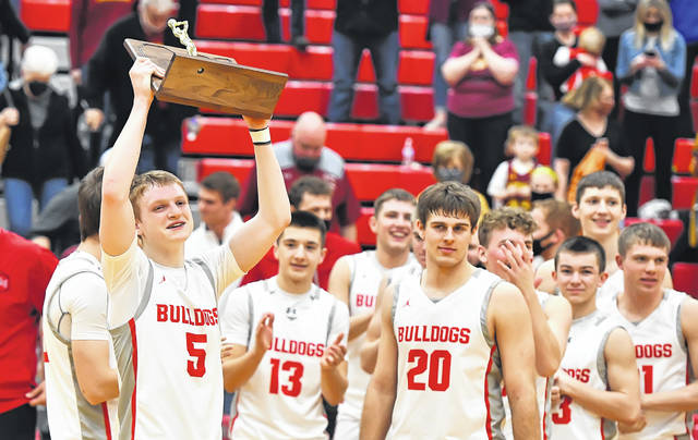 Columbus Grove's Gabe Clement raises the Division IV regional championship trophy Friday night after the Bulldogs defeated New Bremen at Van Wert.