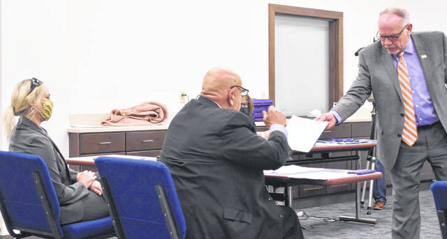 """Allen County Board of Elections Chairman Keith Cheney hands documents to Bradley Kelley, an attorney representing Elizabeth Hardesty, during what was termed a """"quasi-judicial"""" hearing surrounding Hardesty's residency in Lima."""