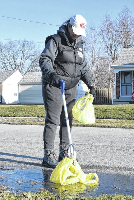 Catheryn Sarno picks up trash as part of a cleanup day Saturday for the Faurot West Neighborhood Association.