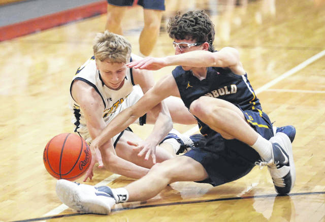 Ottawa-Glandorf's Colin White (22) and Archbold's Alex Roth (4) go for a loose ball in the first quarter of the Division III boys basketball regional semifinal at the Elida Fieldhouse on Wednesday night. More photos at limaohio.com.