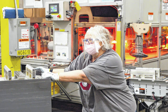 Barb Bailey, a worker at Crown Equipment, wears a mask to protect herself and others.
