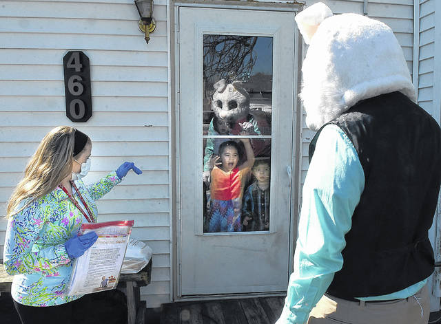 Kindergarten teacher Ainsley Henderson and the Easter Bunny wave goodbye to St. Rose student Anica Ramirez, 5, as St. Rose School teachers and staff dropped off student work last year. This year, pandemic regulations have loosened, so children can enjoy Easter egg hunts and other bunny-themed events in the region.