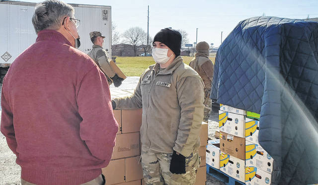 House Speaker Bob Cupp, left, speaks with Ohio National Guard Specialist Masie Utrup, an Ottawa native, during a food distribution Friday at the West Ohio Food Bank on Lima's Kibby Street.