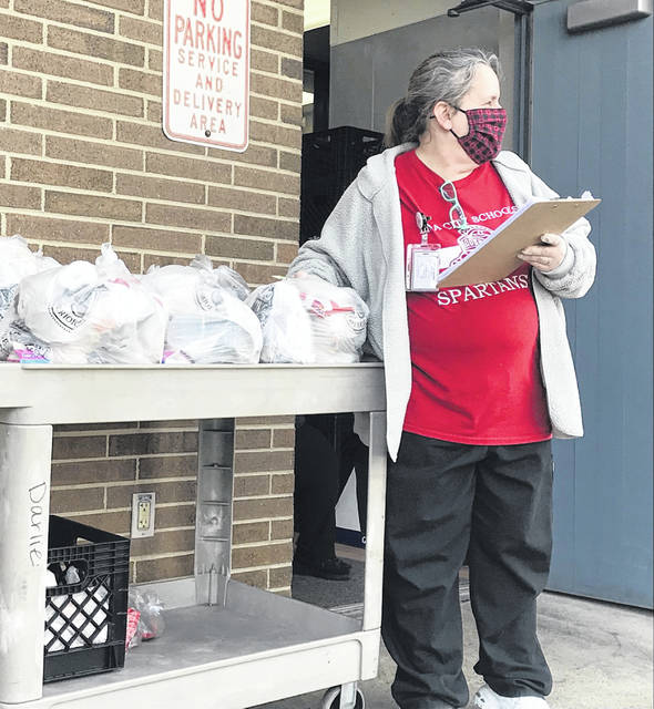 Mindy Cole, food service manager at North Middle School, waits for parents to pick up their children's free meals available for students enrolled in remote classes.