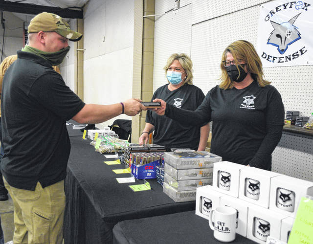 Pat Sullivan, Candy Risner and Jen Nagel of Greyfox Defense LLC were ready to serve customers at the Tri-State Gun Collectors Show on Saturday at the Allen County Fairgrounds.
