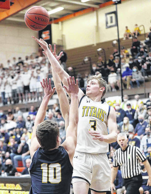 Ottawa-Glandorf boys basketball #3 Brennen Blevins goes up and over Archbold boys basketball #10 D.J. Newman (front) and Archbold boys basketball #4 Alex Roth(rear) during the division lll Regional semi-final at Elida Field house on March 10,2021 more photos at limaohio.com