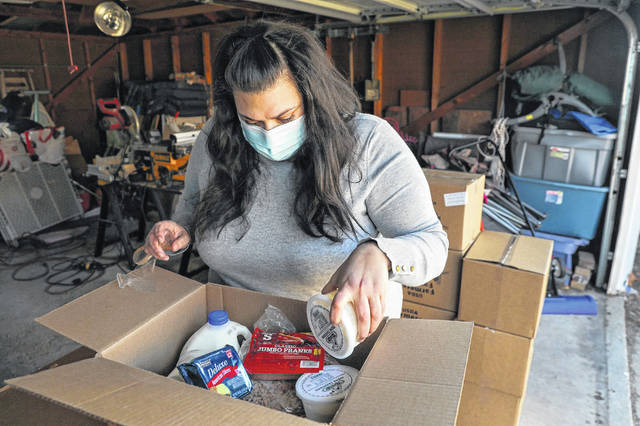 Karen Krausen-Ferrer, who volunteers with the West Ridge Community Response Team, looks over one of the 20 boxes of food Friday that was dropped off at her garage in Chicago. She coordinates the food boxes and makes sure they are all delivered.  (Jose M. Osorio/Chicago Tribune/TNS)