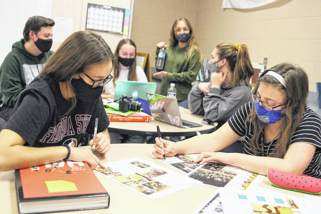 """From left, Mitchell High yearbook editors Cate Miller, Jillian Misemer and Sophia Henges work on page layouts for their 2021 publication, """"Stampede."""""""