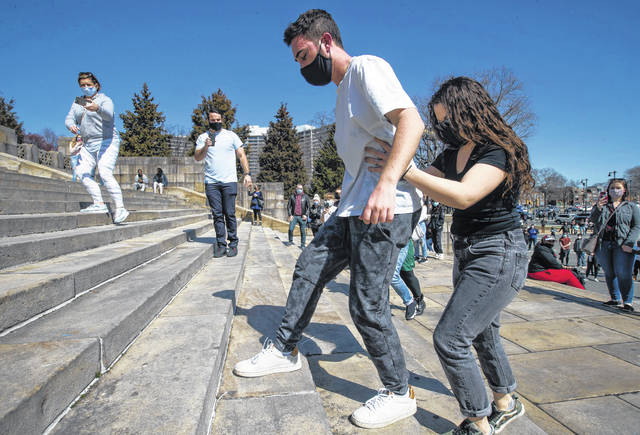 Chase Friedman makes his way up the Art Museum steps as his physical therapist, Erin Freimuth from Magee Rehabilitation Hospital, lends support on Saturday afternoon.  (Charles Fox/Philadelphia Inquirer/TNS)