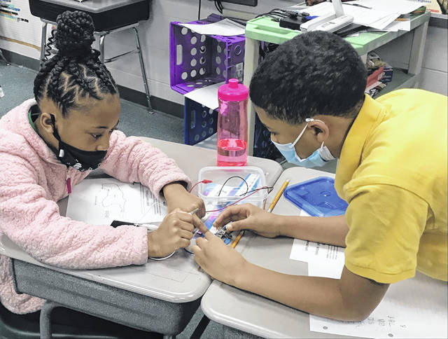 Liberty Arts students Somaya Simpson, left, and Major Amerson try to light a lightbulb by building an electrical circuit during a presentation by Science Enhancement and Science Advancement.