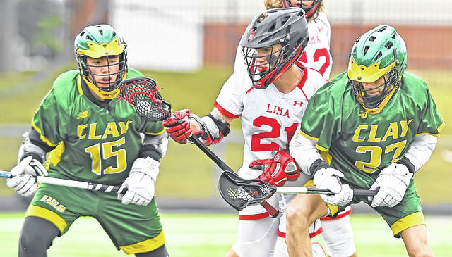 Lima Senior's Aaron Bowsher, center. runs with the ball between Oregon Clay's Kareem Tawil, right, and Nathaniel Saurbeck during Friday's game at Spartan Stadium. See more lacrosse photos at LimaScores.com.
