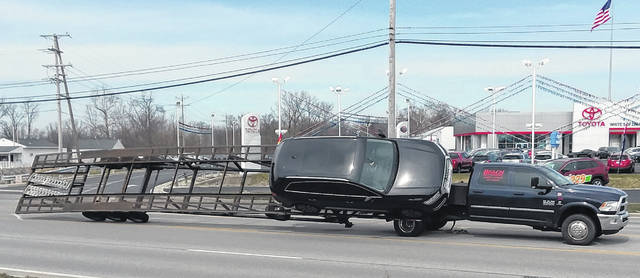 Elida Road in front of White Toyota was blocked for a time Wednesday after a pickup truck transporting a vehicle nearly ended up on its side.