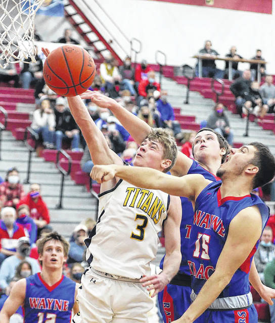 Ottawa-Glandorf's Brennen Blevins puts up a shot against Wayne Trace's Trevor Speice (15) and Cameron Graham during Saturday's Division lll district final at Lima Senior. See more district photos at LimaScores.com. Don Speck | The Lima News